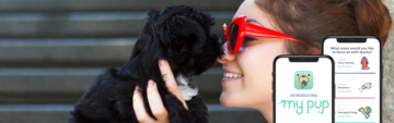 girl with red sunglasses nose to nose with a black puppy